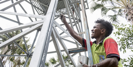 A worker repaints a water tower, Kasait, Timor-Leste (Michael Coyne)