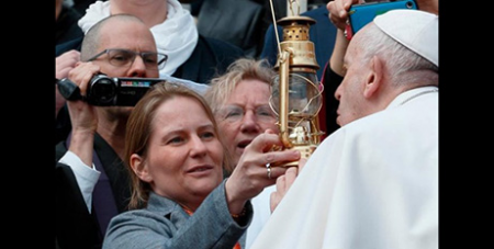 Pope Francis blows on a flame of peace presented by the an activist organisation during his general audience in St Peter's Square yesterday (CNS/Paul Haring)