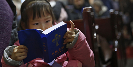 Reading a Bible in the state-approved Catholic cathedral in Beijing (CNS/How Hwee Young)
