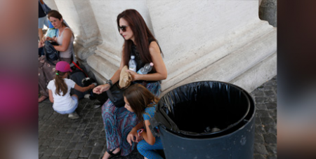 A woman with plastic water bottles under the St Peter's Square colonnade (CNS/Paul Haring)