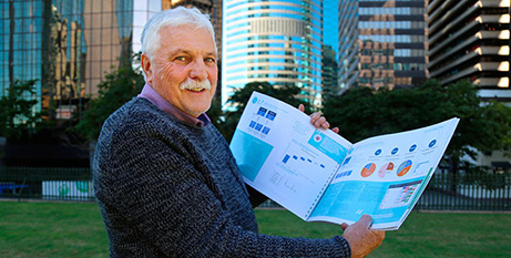 Rick Dalmau displays an energy report from one of the pilot schools (The Catholic Leader/Mark Bowling)
