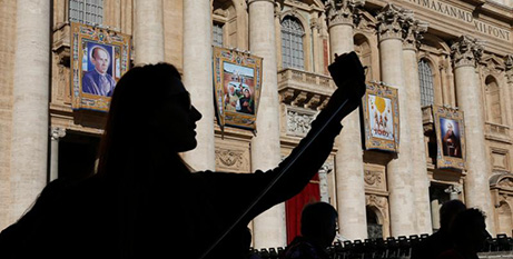 A woman takes a selfie in front of the banners of the new saints (CNS/Paul Haring)