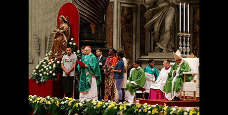 Pope Francis reads a letter to young people during the closing Mass of the Synod (CNS/Paul Haring)