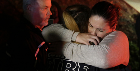 A woman who fled the Borderline Bar and Grill is comforted by a first responder-CNS-Mike Nelson-EPA
