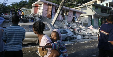 People in Port au Prince, Haiti, walk past buildings destroyed by the earthquake in this 2010 photo (CNS/Eduardo Munoz, Reuters)