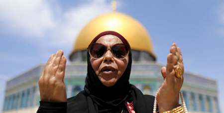 A Palestinian woman prays in front of the Dome of the Rock in Jerusalem's Old City on April 16 (CNS/Reuters, Ammar Awad)