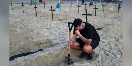 An activist digs graves on Copacabana beach, Rio de Janeiro, to symbolise Brazilians who have died from COVID-19 (CNS/Pilar Olivares Reuters)