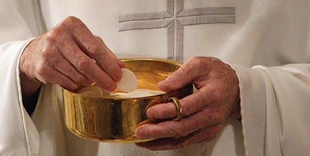 A priest prepares to distribute Communion during Mass in Washington (CNS/Bob Roller)