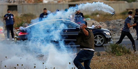 A Palestinian demonstrator throws a tear gas canister near the Jewish settlement of Beit El during a protest on Wednesday against the annexation (/Mohamad Torokman, Reuters)