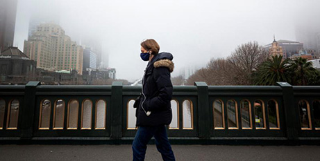 A person in a protective face mask walks along the Princes Bridge in Melbourne, July 17 (CNS/Daniel Pockett, Reuters)