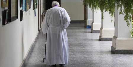An elderly priest walks to his residence at Our Lady of Carmen Church in Panama City (CNS/Bob Roller)