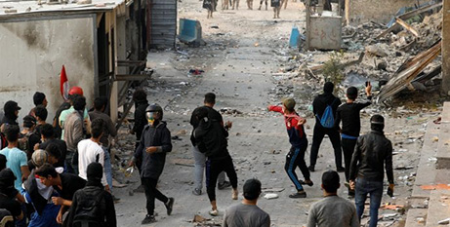 Demonstrators throw stones at security forces during an anti-government protest in Baghdad on Friday (CNS/Khalid al Mousily, Reuters)