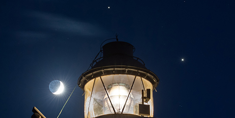 Saturn is seen shining above a lighthouse in Syracuse, Sicily, and Jupiter is seen shining to the right, in this photo taken in November (CNS/Kevin Saragozza, courtesy NASA)